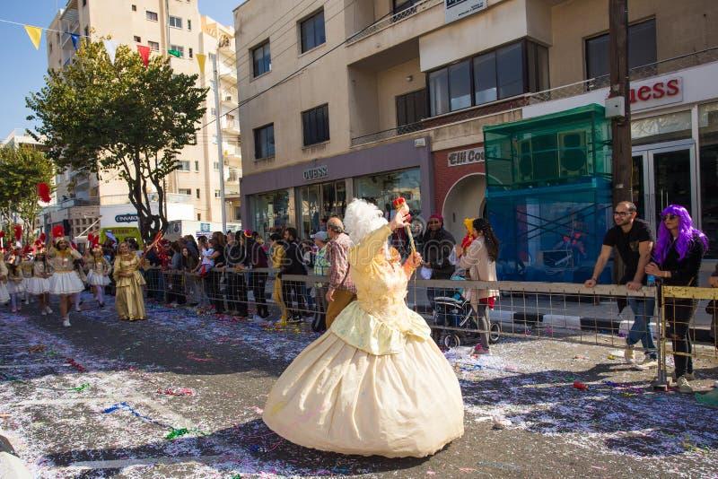LIMASSOL CYPERN - FEBRUARI 26: Carnivalists i hattar för en silvercylinder följer joyfully den Limassol kommunmusikbandet royaltyfri bild