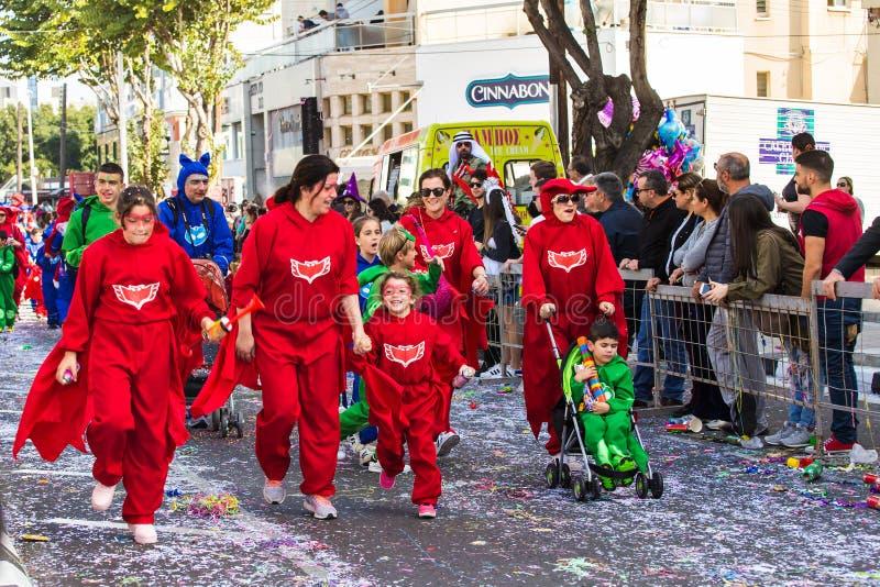 LIMASSOL CYPERN - FEBRUARI 26: Carnivalists i hattar för en silvercylinder följer joyfully den Limassol kommunmusikbandet royaltyfria foton