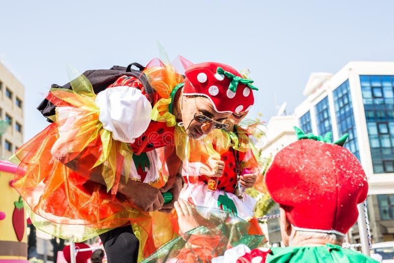 LIMASSOL CYPERN - FEBRUARI 26: Carnivalists i hattar för en silvercylinder följer joyfully den Limassol kommunmusikbandet arkivfoto