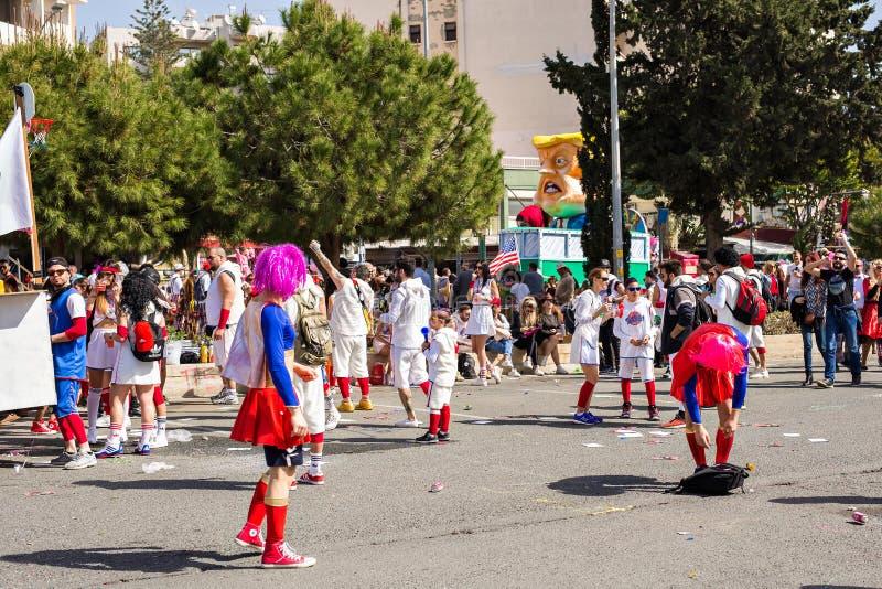LIMASSOL CYPERN - FEBRUARI 26: Carnivalists i hattar för en silvercylinder följer joyfully den Limassol kommunmusikbandet arkivfoton