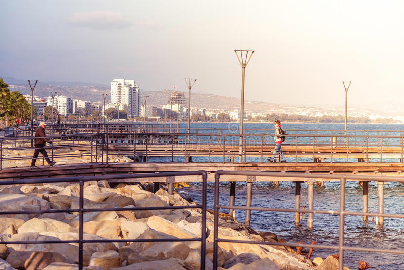 LIMASSOL, CYPRUS - March 08, 2016: Limassol's seafront wooden pi. Ers with walking people royalty free stock image