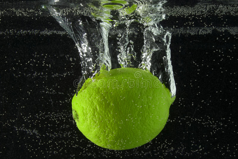 Lime. A lime submerges in water with bubbles stock photo