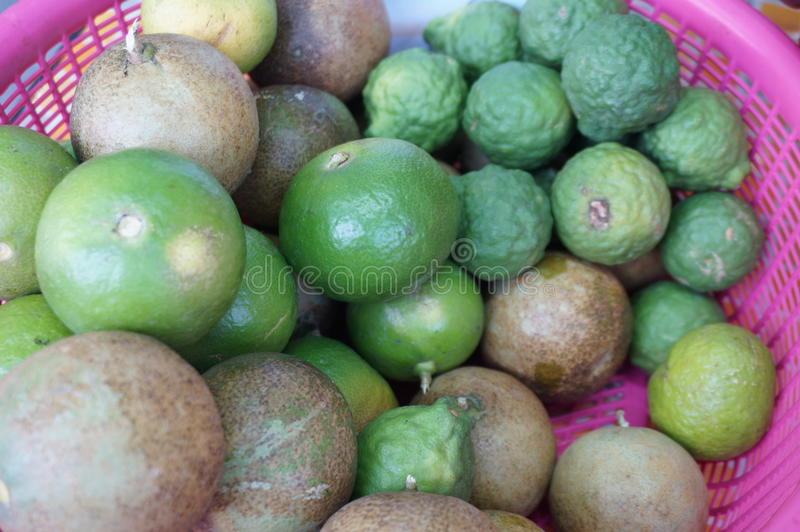 Lime and Bergamot. Close up of photo of very fresh green limes and bergamot & x28;Sweet kaffir lime, Leech Lime& x29; in pink basket royalty free stock photography