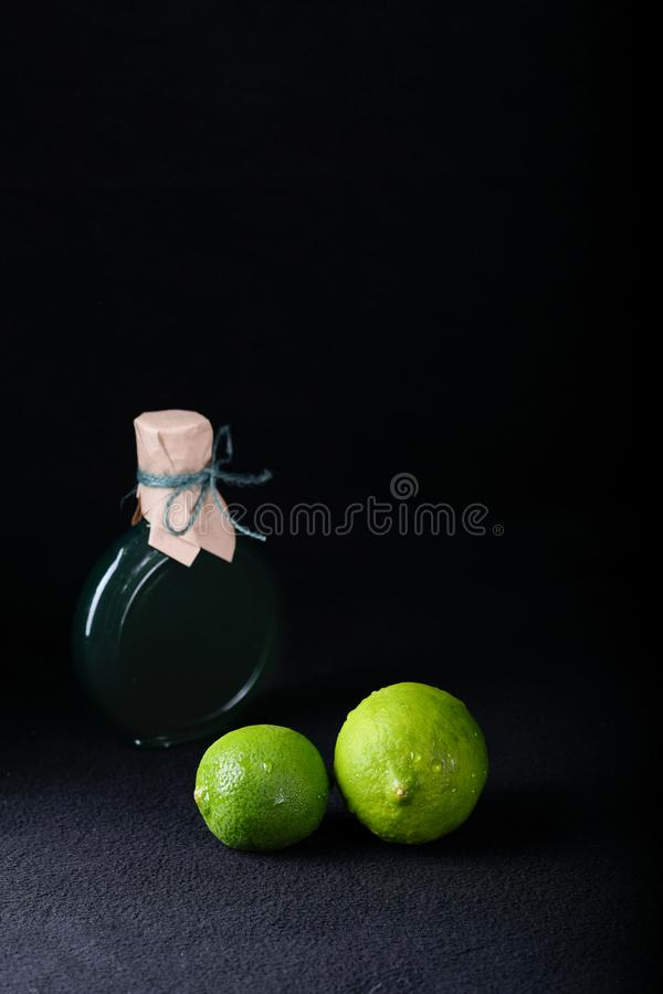 LIME ON A BLACK BACKGROUND WITH A BOTTLE OF LIME OIL royalty free stock photography