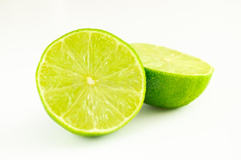 Lime cut in two halves of green color on white background royalty free stock images