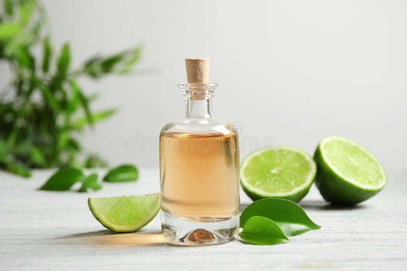 Lime essential oil and cut citrus fruits on white table fotografia stock