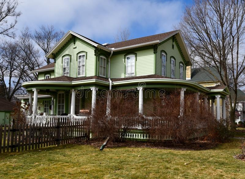 Lime Green Italianate. This is a Spring picture of a lime green house located in Oconomowoc, Wisconsin. This wood house was built in 1860, is an example of royalty free stock photo