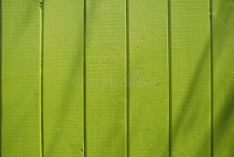 Lime Green Plank Fence. A green painted fence of vertical planks in bright sunlight with soft shadows from a palm tree stock photos