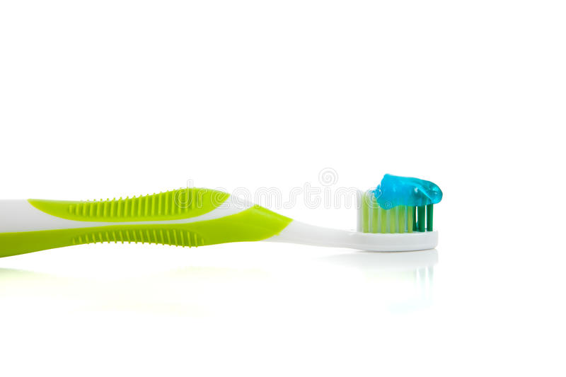 Lime green toothbrush and toothpaste on white. A lime green toothbrush and blue gel toothpaste on a white background stock photos