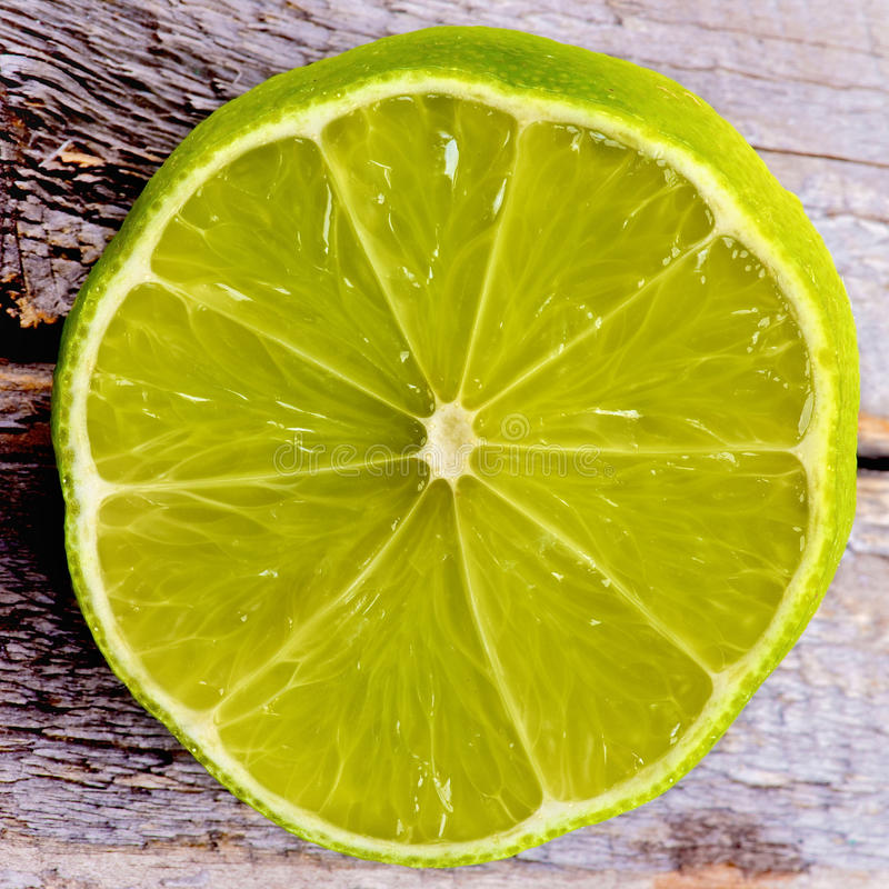 Lime. Half of Green Lime Cross Section closeup on Wooden background stock photo