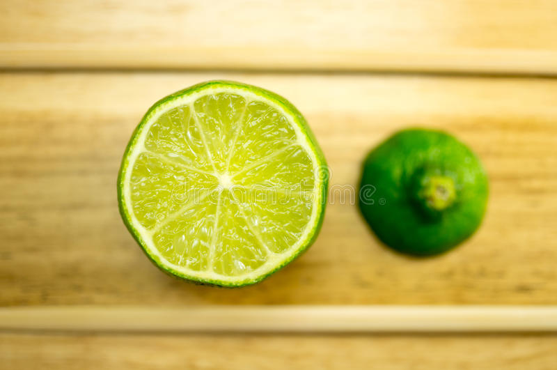 Lime. Half on a wooden board closeup stock image