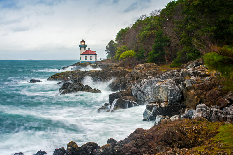 Lime Kiln Lighthouse. The Lime Kiln Lighthouse is located on the edge of Haro Strait on San Juan Island, Washington. This was a stormy winters day with waves stock image