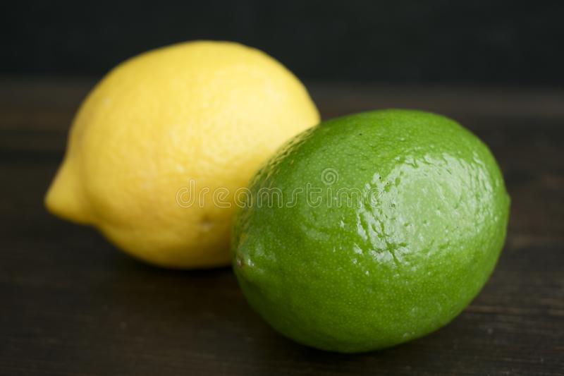 Lime and Lemon  on a Dark Wood Background. A closeup view of citrus fruit on a dark wood background royalty free stock image