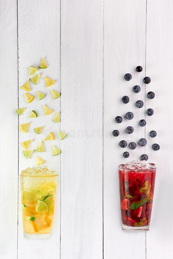 Lime and lemon lemonad and red berry tea at white wooden table top. Creative summer cocktails concept with copy space stock photography