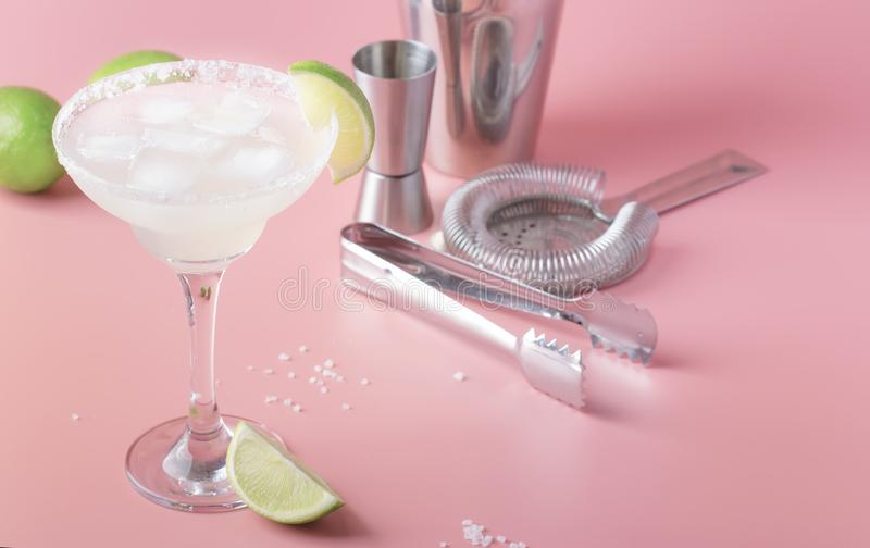 Lime margarita alcoholic cocktail with silver tequila, liqueur, lime juice, sugar syrup, salt and ice, festive trendy pink. Background, copy  space royalty free stock photos