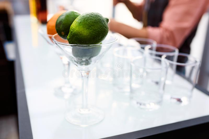 Lime and orange martini glasses and glass cups. Lime and orange martini glasses and empty glass cups stock image