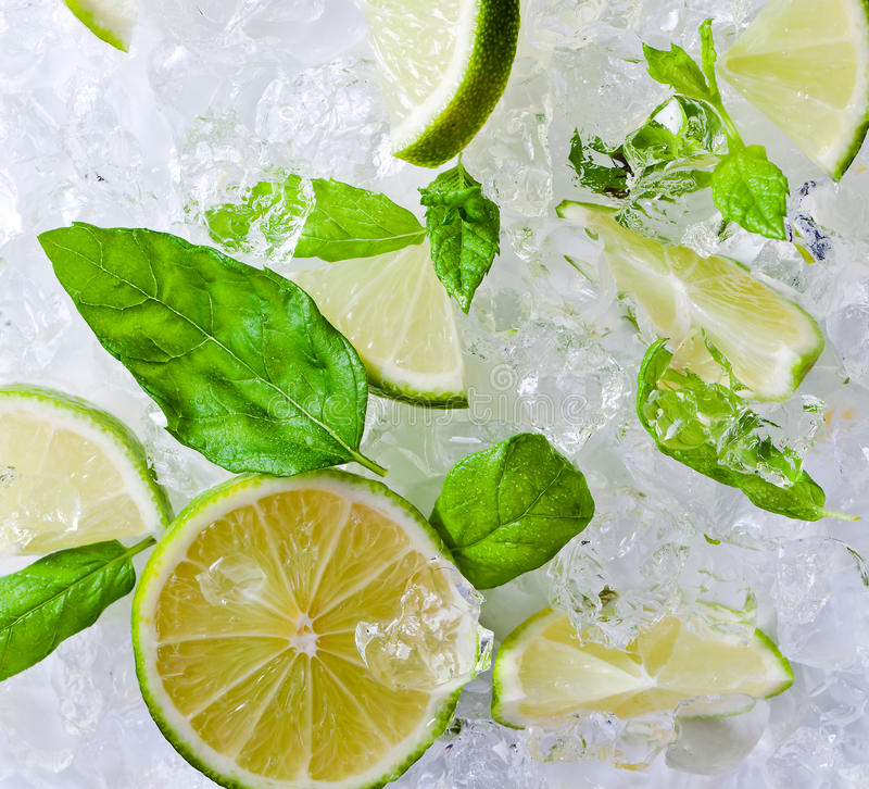 Lime and peppermint with ice. Lime pieces and leaves of mint with ice royalty free stock photo