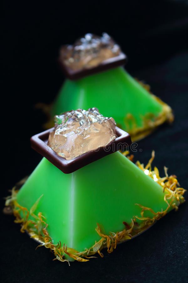 Lime pyramid dessert with aloe vera jelly and flower petals on black background royalty free stock image