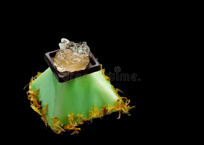 Lime pyramid dessert with aloe vera jelly and flower petals stock images