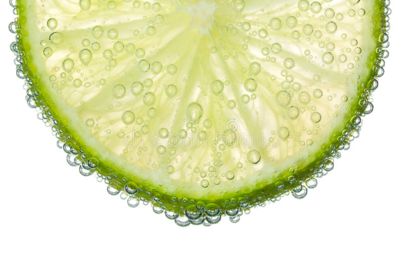 Lime Slice in Clear Fizzy Water Bubble Background stock photography