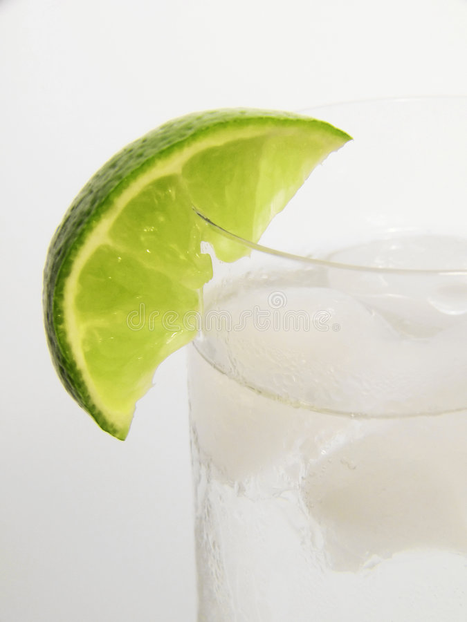 Lime Wedge In Glass Stock Images
