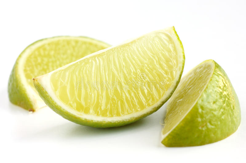 Lime wedges. Arranged on a white surface. Selective focus stock image