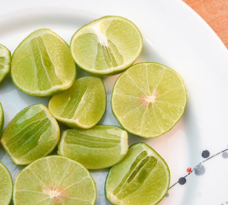 Limefrukt i den vita maträtten på träblackground arkivfoto