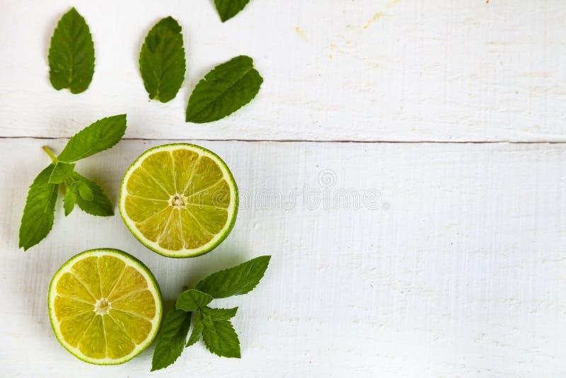 Limefrukt och mintkaramell på en vit tabell royaltyfri fotografi