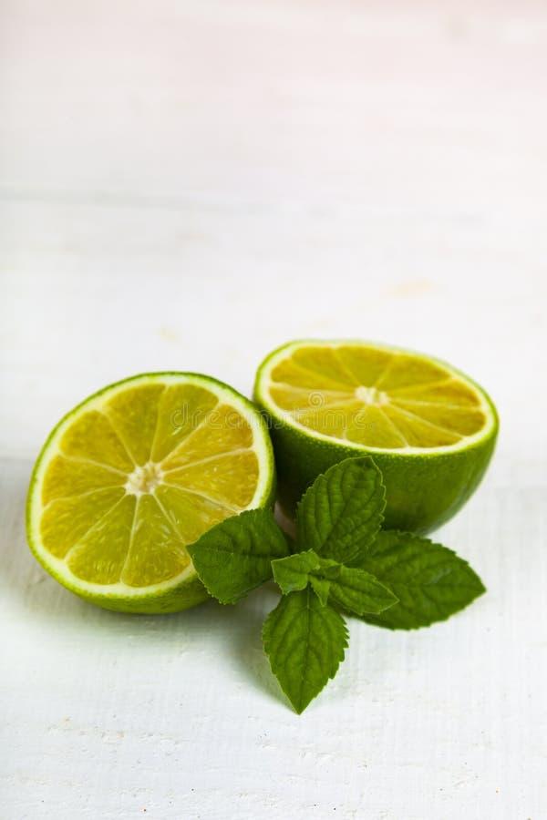 Limefrukt och mintkaramell på en vit tabell royaltyfri foto