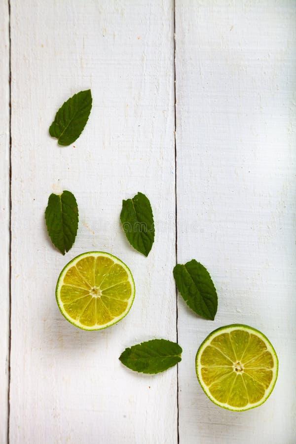 Limefrukt och mintkaramell på en vit tabell royaltyfri bild