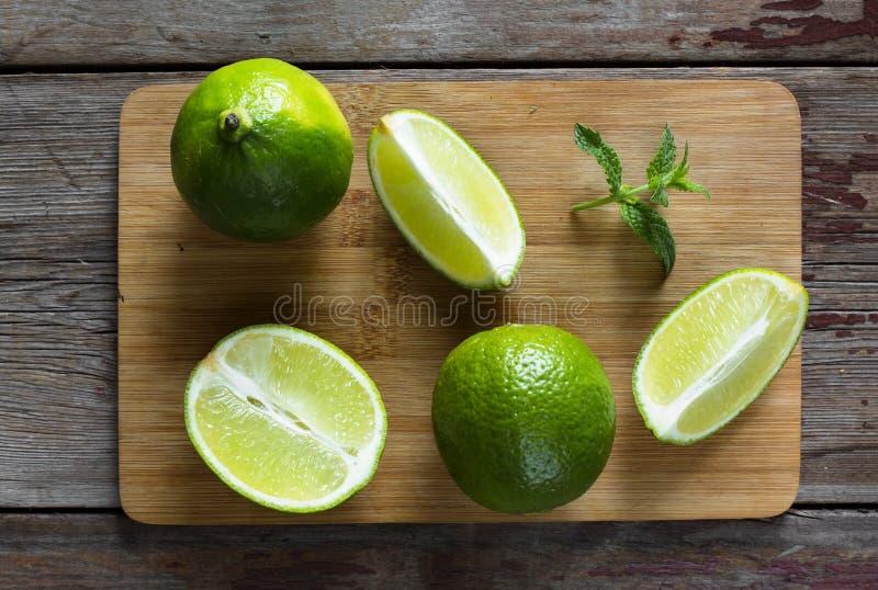 Limefrukt och mintkaramell på kökbrädet Limefrukt, hela frukter och skivade skivor royaltyfria foton