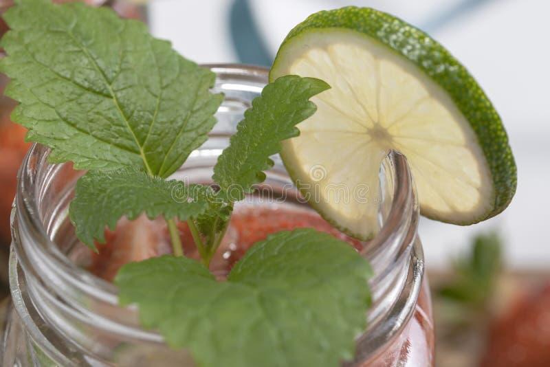 Limefrukt och sidor av den gröna mintkaramellen på halsen av ett exponeringsglas rånar för frukt som leder, närbild royaltyfri fotografi