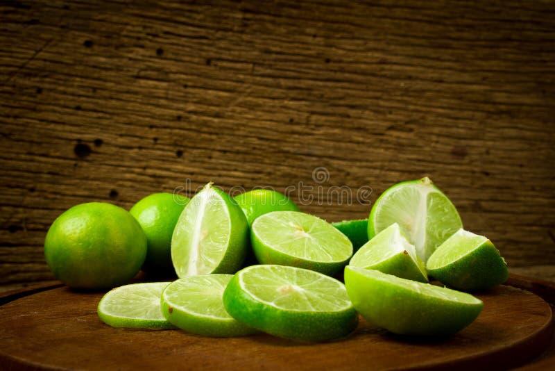 limefrukt på choppping brädeträ på trä Wood bakgrund arkivfoton