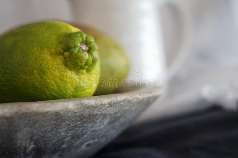 Limefrukt som är nära upp i stenbunke royaltyfri fotografi