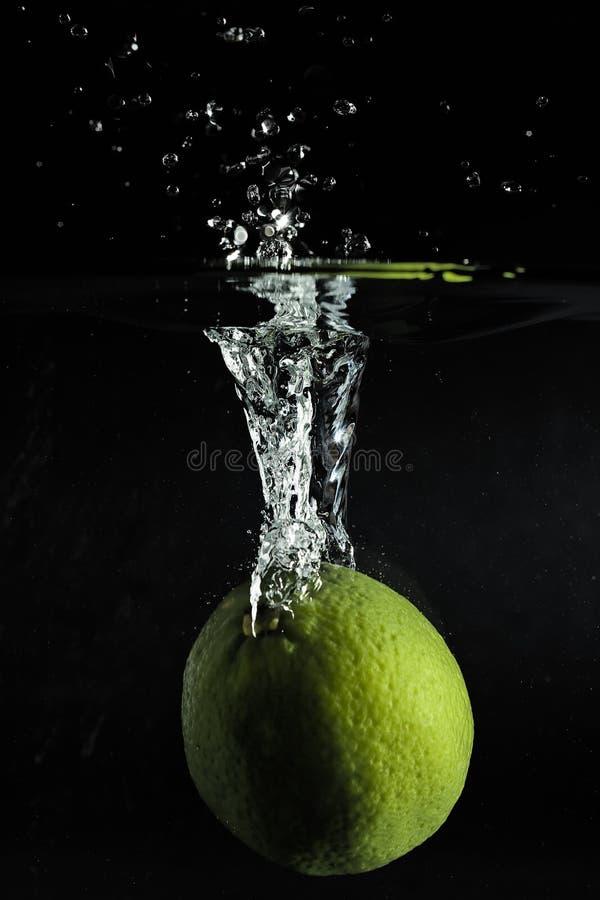 Limefrukt som tappas i vatten i mörkt rum royaltyfri fotografi