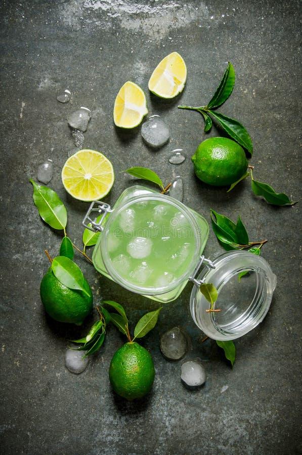 Limefruktbakgrund Fruktsaften från limefrukterna med is och skivade limefrukter omkring royaltyfri foto