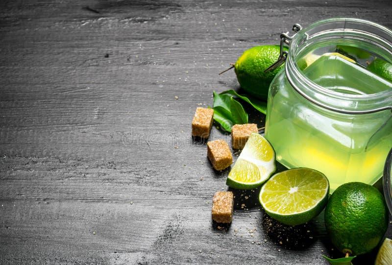 Limefruktbakgrund Fruktsaften från limefrukterna, sockret och skivorna av limefrukt arkivfoton
