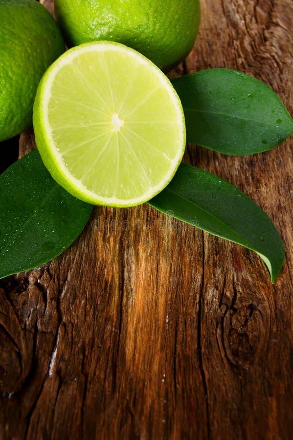 Limefrukter. På träbräde. royaltyfria foton