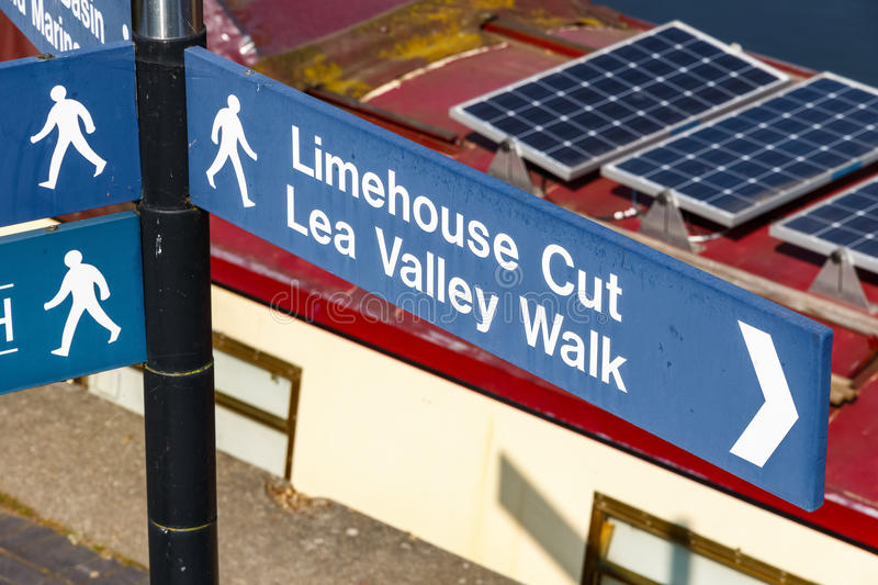 Limehouse Cut and Lea Valley Walk street sign. In London with a narrowboat in the backgroun royalty free stock photography