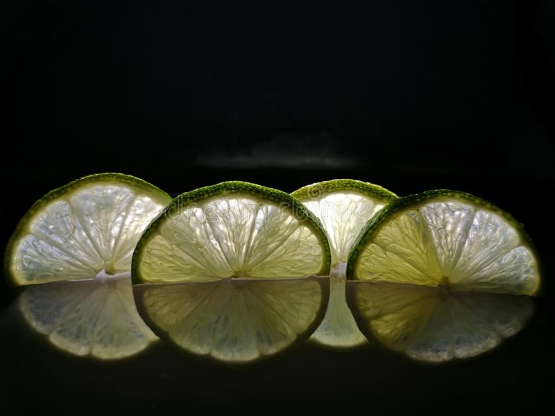 Limes in cut. Limes cut on black background royalty free stock photography
