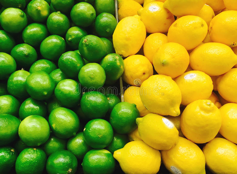 Limes and lemons in the supermarket stock image