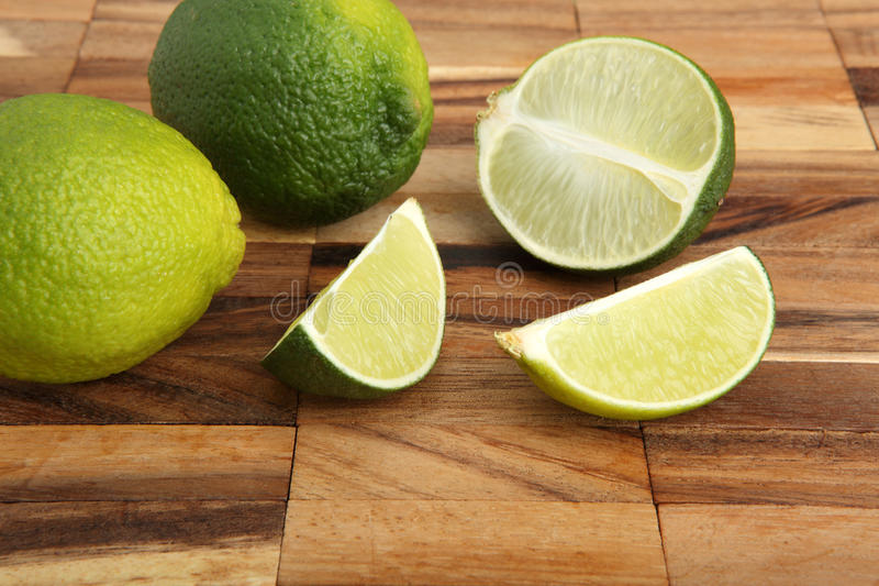Download Limes And Lime Slices On A Wooden Pad Stock Photo - Image: 28917316