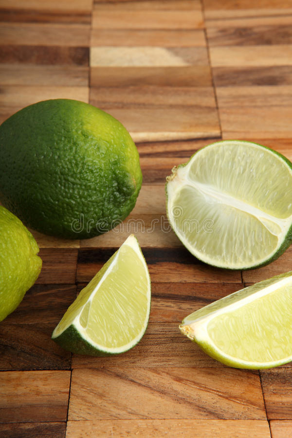 Download Limes And Lime Slices On A Wooden Pad Stock Photo - Image: 28917380