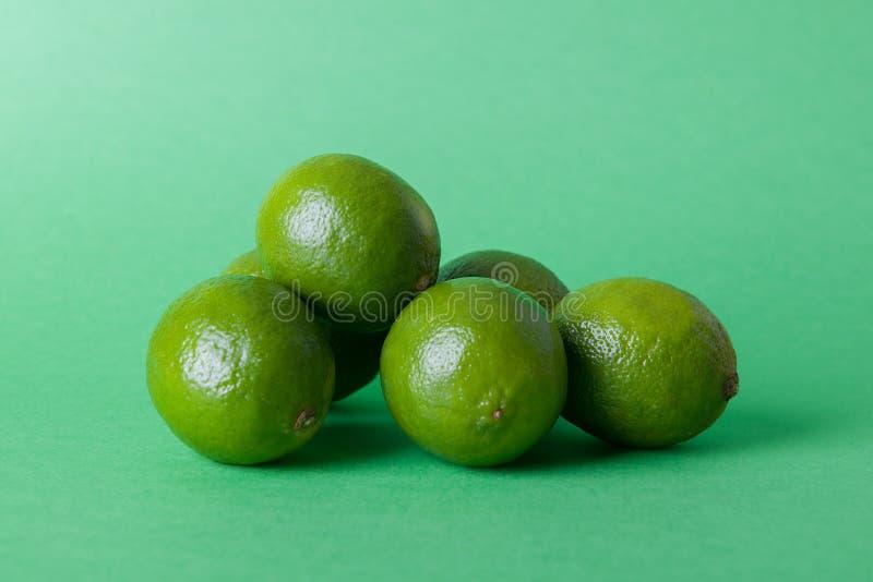 Limes_oranges_lemon_stock_pictures. Glass bowl of citrus, orange, lime, lemon fruits on a coloured background stock images