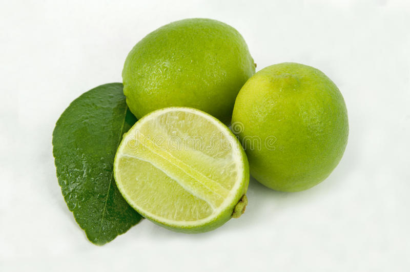 Limes with slices and leaves. On white background stock photos