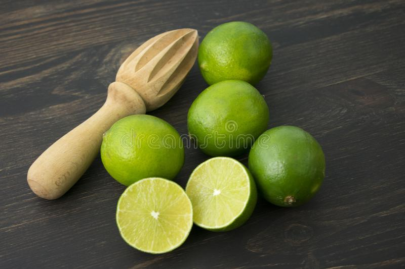 Limes on a Wood Cutting Board. Closeup view of halved and whole limes with a citrus reamer on a dark wood background royalty free stock images