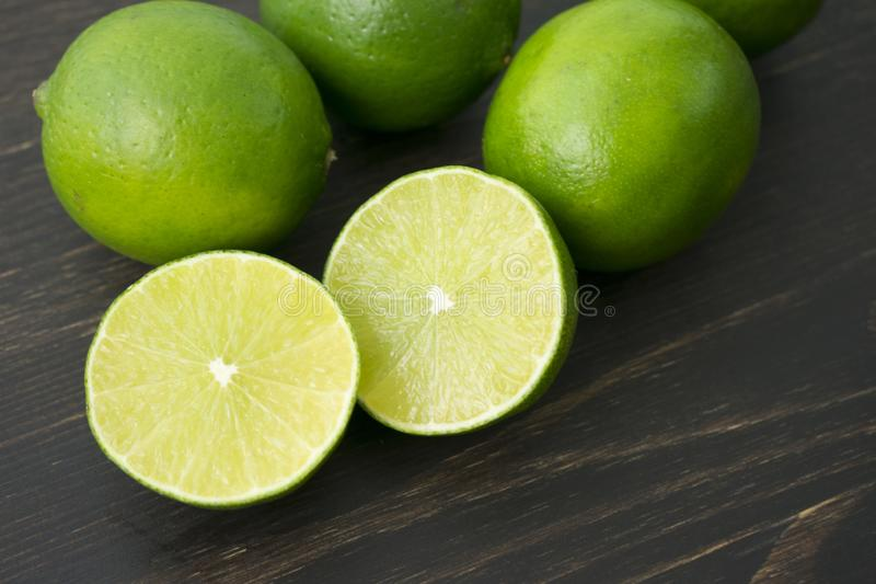 Limes on a Wood Cutting Board. Closeup view of halved and whole limes on a dark wood background royalty free stock image