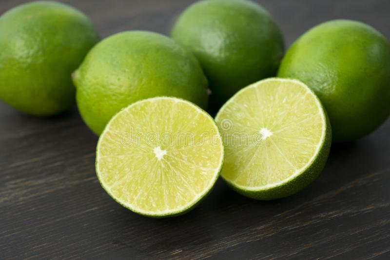 Limes on a Wood Cutting Board. Closeup view of halved and whole limes on a dark wood background stock photo
