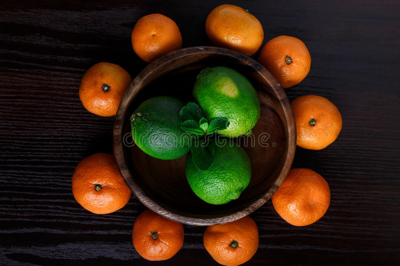 Limes in wooden plate with mandarines and mint leafs on dark background close-up macro royalty free stock photo