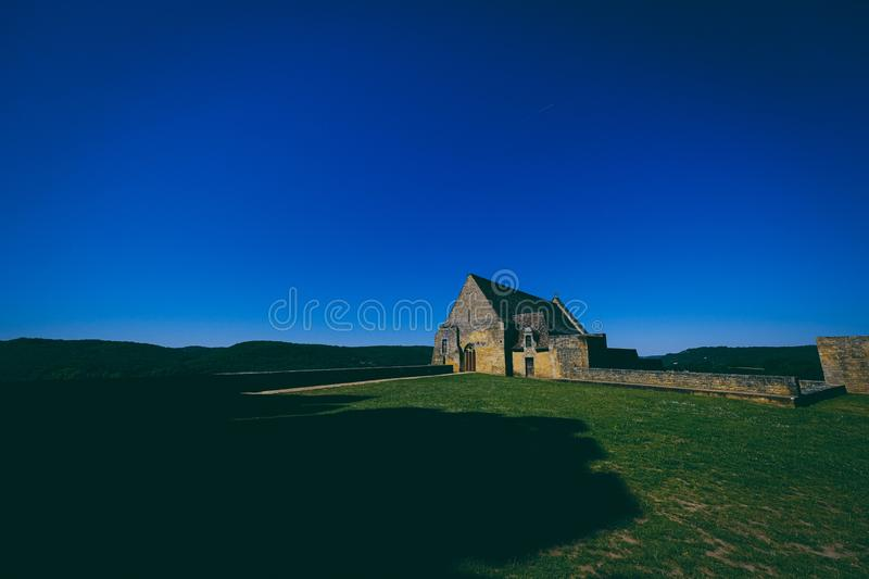 Limestone building near the grassy field with clear blue sky in the background royalty free stock photo